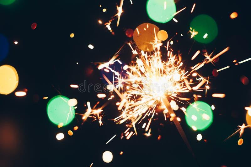 Palillos chispeantes de las bengalas de Bengala en llamas en un fondo negro con el bokeh de las luces fondo del Año Nuevo del tem imágenes de archivo libres de regalías