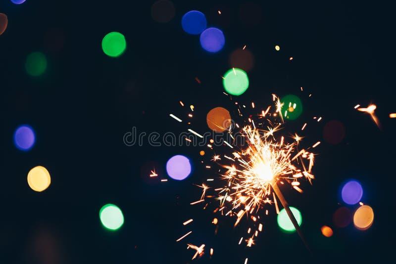 Palillos chispeantes de las bengalas de Bengala en llamas en un fondo negro con el bokeh de las luces fondo del Año Nuevo del tem imagen de archivo