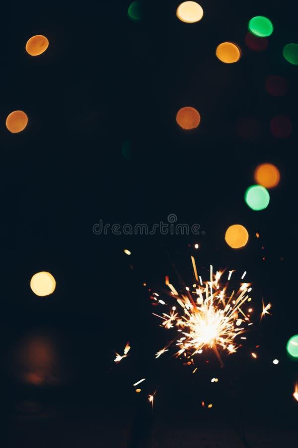 Palillos chispeantes de las bengalas de Bengala en llamas en un fondo negro con el bokeh de las luces fondo del Año Nuevo del tem fotos de archivo libres de regalías