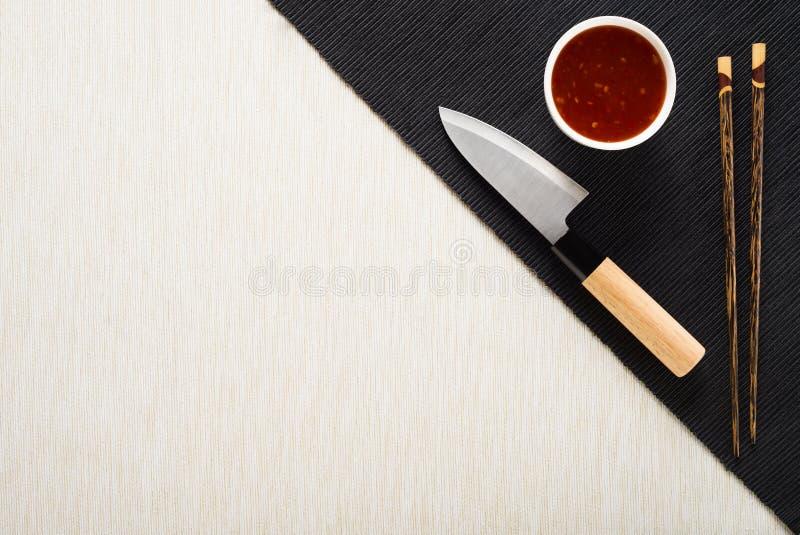 Palillos, cuchillo y cuenco con la salsa en la estera de tabla fotografía de archivo