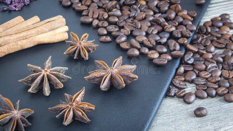 Palillos de canela, anís de estrella y granos de café Especias y comida en fondo de madera Ingredientes para el restaurante foto de archivo
