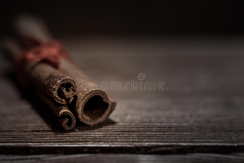 palillos de canela atados con guita y polvo en cuenco, en la tabla de roble rústica imagenes de archivo