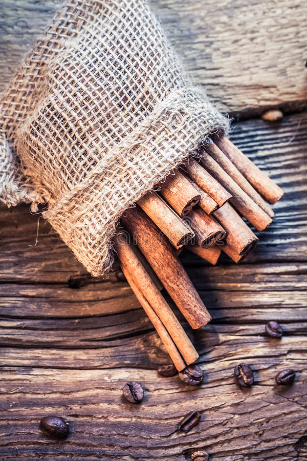 Palillos de canela en un saco de la arpillera en la tabla de madera imagen de archivo