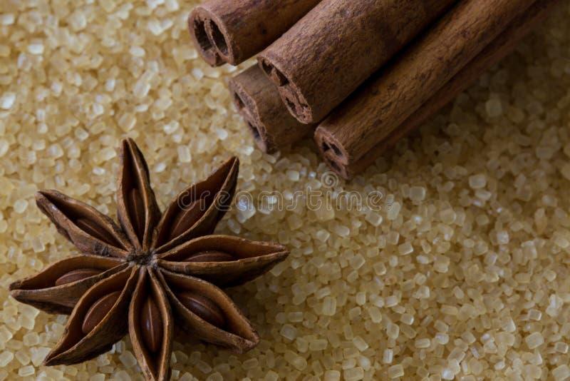 Palillos de la estrella y de canela del anís en fondo marrón de caña de azúcar Vista y detalles macros del azúcar cristalino Visi imágenes de archivo libres de regalías
