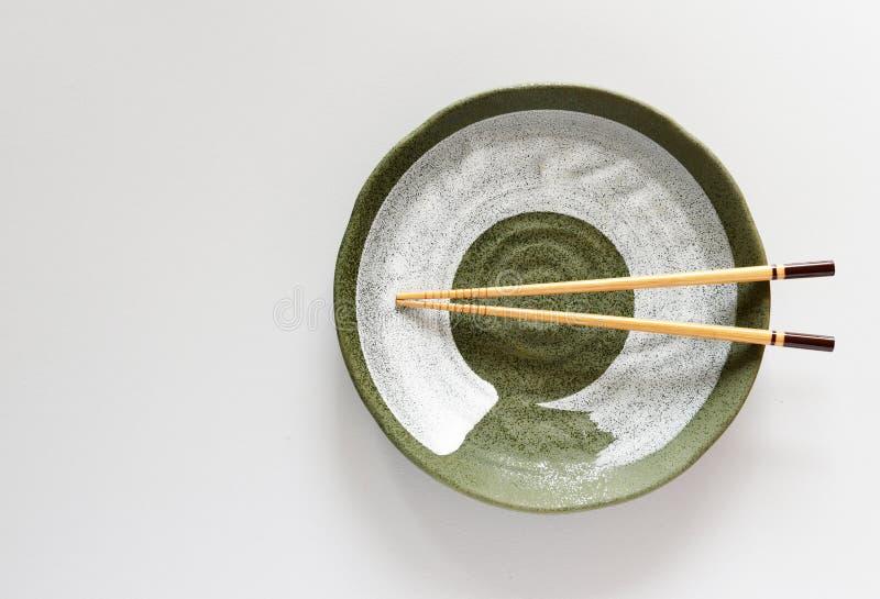 Palillos de madera en el estilo de cerámica de oriental del verde de la placa foto de archivo