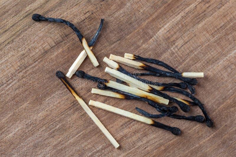 Palillos de madera quemados de los partidos en un fondo de madera de la tabla fotografía de archivo