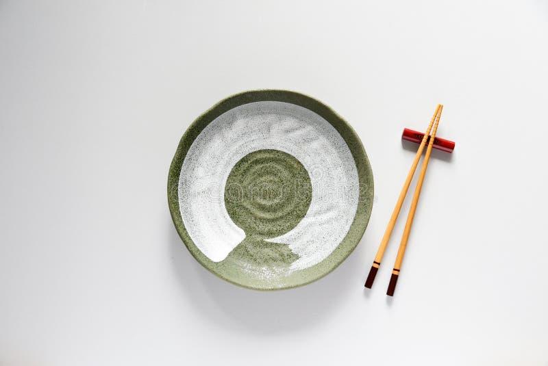 Palillos de madera y estilo de cerámica de oriental del verde de la placa imágenes de archivo libres de regalías