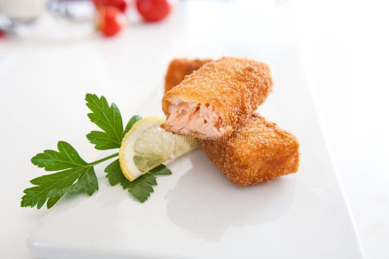 Palillos de pescados de color salmón fritos con el limón y el perejil en una placa blanca fotografía de archivo