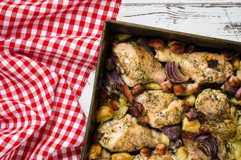 Palillos de pollo asados con tocino, la cebolla y el ajo fotografía de archivo