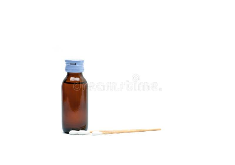 Palillos del algodón y soluciones antisépticas en la ISO ambarina de la botella de cristal fotos de archivo