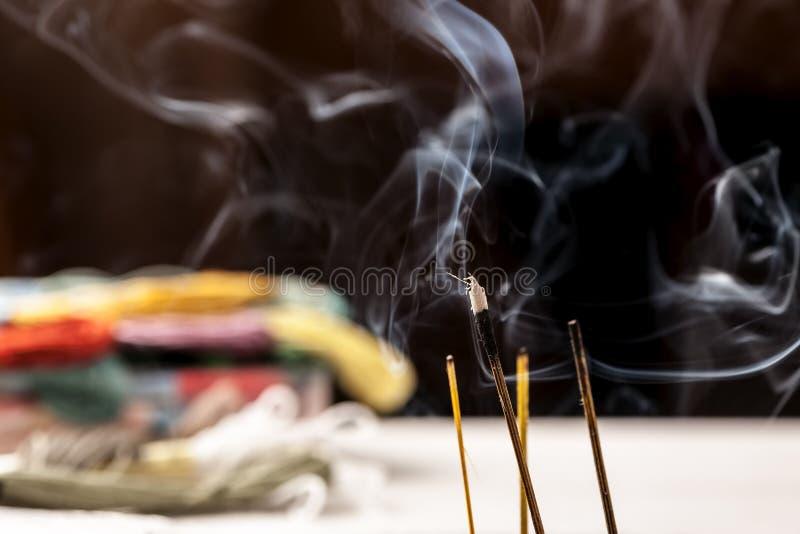 Palillos del incienso que arden con el tiro del primer del humo fotografía de archivo
