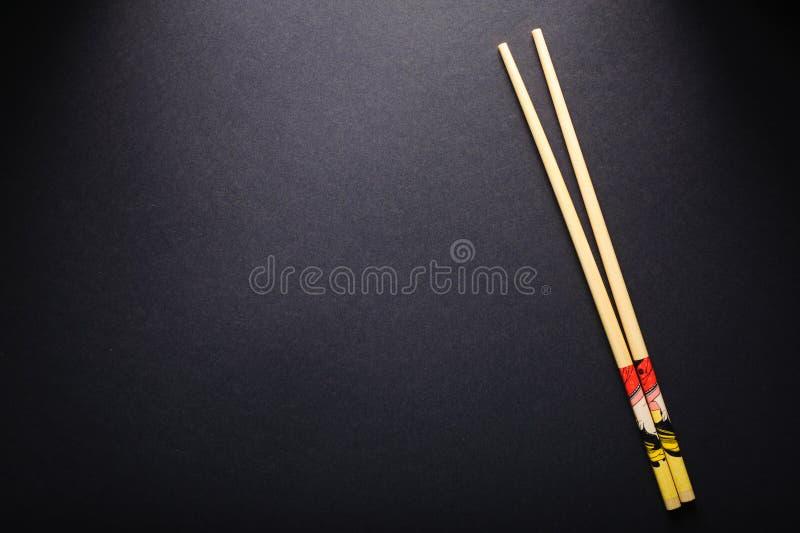 Palillos del sushi en espacio negro de la copia del fondo imagen de archivo