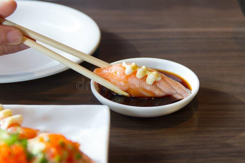 Palillos del uso de la gente para coger el sushi foto de archivo libre de regalías