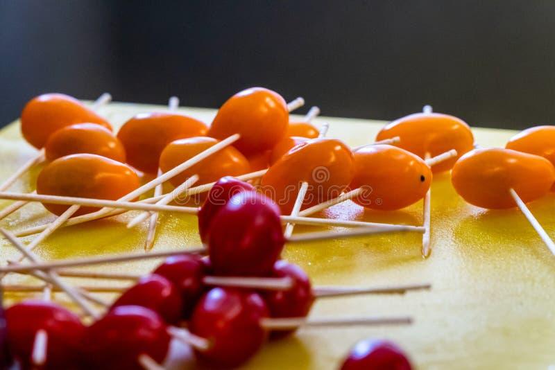 Palillos en los pequeños tomates para las pequeñas hamburguesas en la tajadera amarilla imágenes de archivo libres de regalías