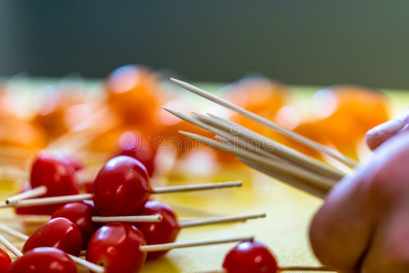 Palillos en los pequeños tomates para las pequeñas hamburguesas en la tajadera amarilla imagen de archivo