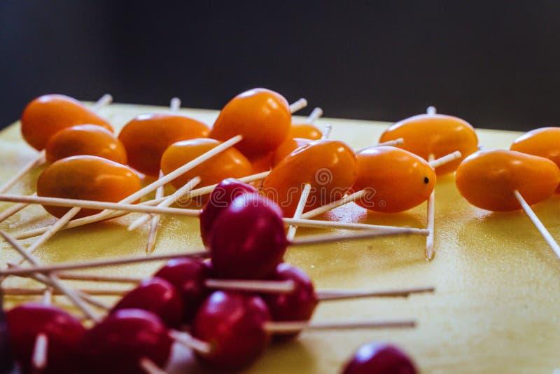 Palillos en los pequeños tomates para las pequeñas hamburguesas en la tajadera amarilla - sistema de la cocina fotografía de archivo libre de regalías