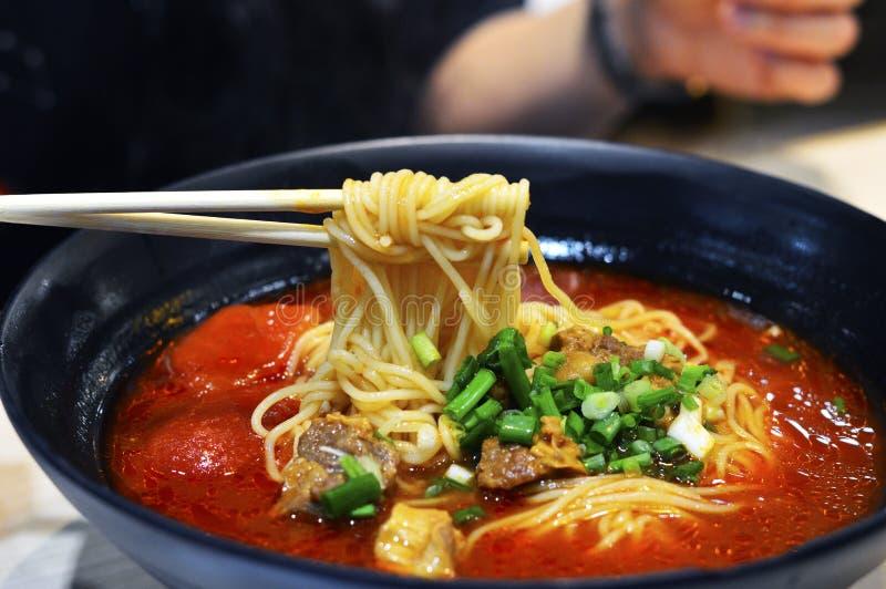 Palillos Pcik encima de la sopa de fideos china de la carne de vaca del tomate imágenes de archivo libres de regalías