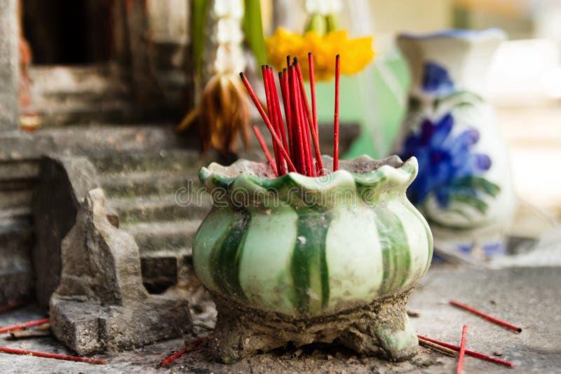 Palillos rojos del incienso aromático en el pote de arcilla para rogar a Buda fotografía de archivo