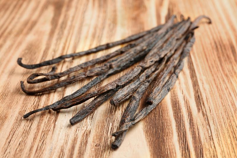 Palillos secados de la vainilla en fondo de madera imagenes de archivo