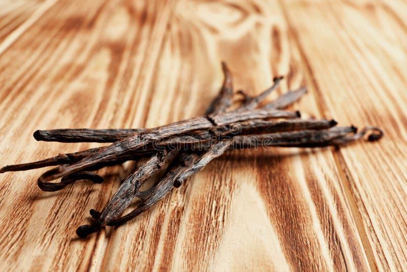 Palillos secados de la vainilla en fondo de madera imagen de archivo libre de regalías