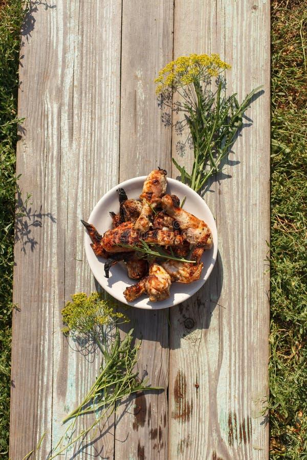 Palillos y alas asados a la parrilla sabrosos de pollo en una placa blanca, visión superior foto de archivo libre de regalías