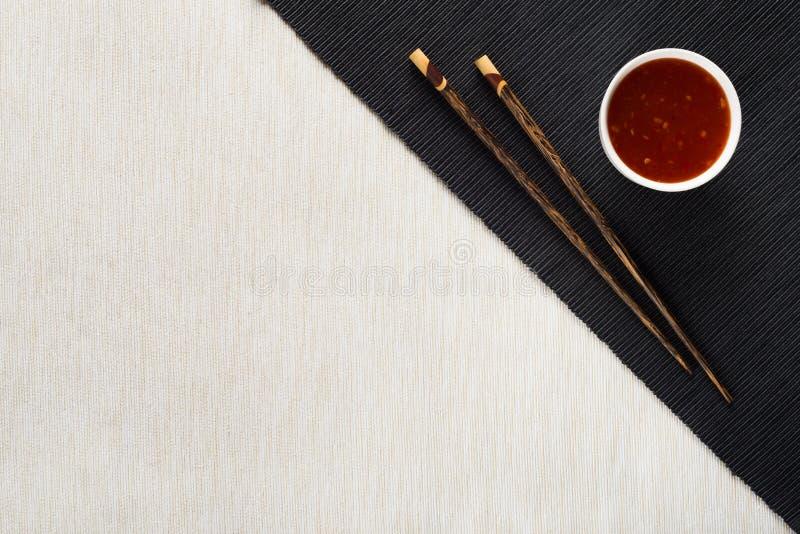 Palillos y cuenco con la salsa en la estera de tabla imágenes de archivo libres de regalías