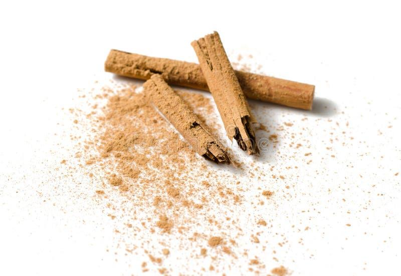 Palillos y polvo de canela en blanco fotografía de archivo libre de regalías