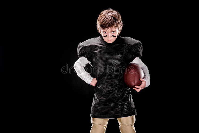 Palla arrabbiata della tenuta del giocatore di football americano del ragazzo ed esaminare macchina fotografica immagini stock libere da diritti