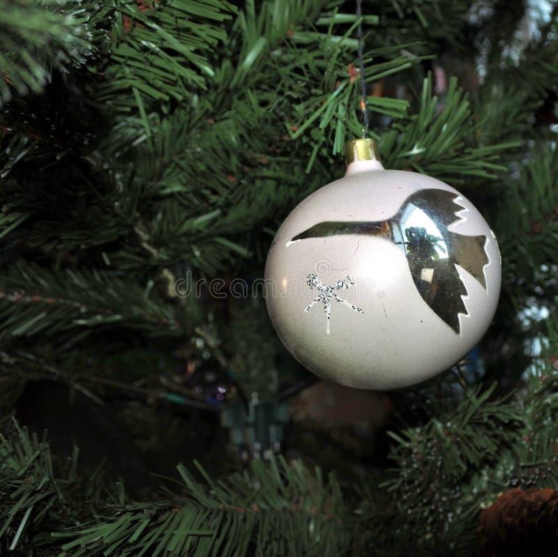 Palla bianca con un'immagine della gru giocattoli d'annata di natale sul fondo dell'albero del nuovo anno immagini stock