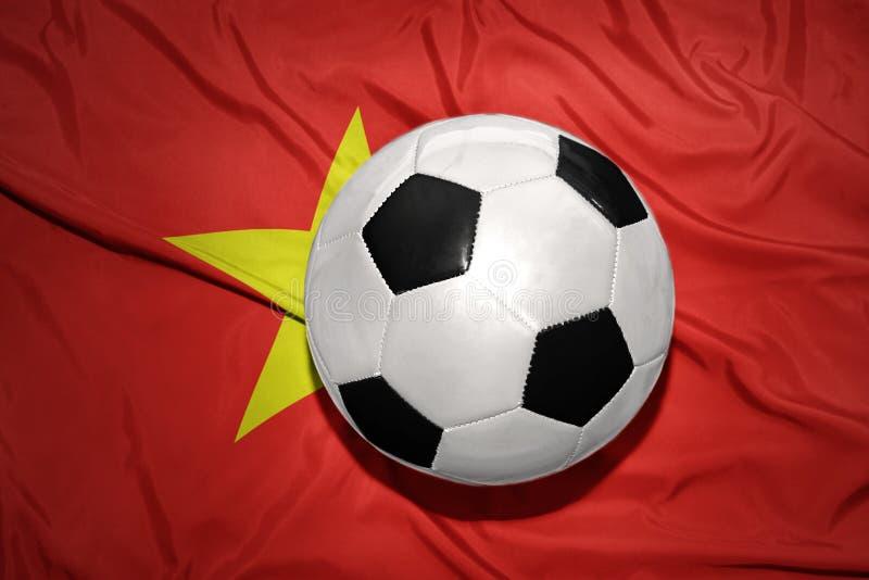 Palla in bianco e nero di calcio sulla bandiera nazionale del Vietnam fotografia stock libera da diritti