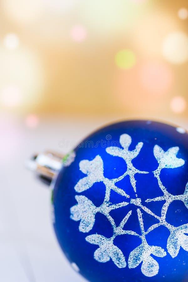 Palla blu di Natale con il fondo dorato con le luci variopinte del chiarore dei coriandoli, spazio della neve dell'ornamento bian fotografie stock