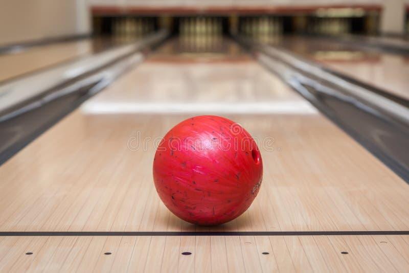 Palla da bowling rossa sulla pista nel centro di bowling immagini stock libere da diritti