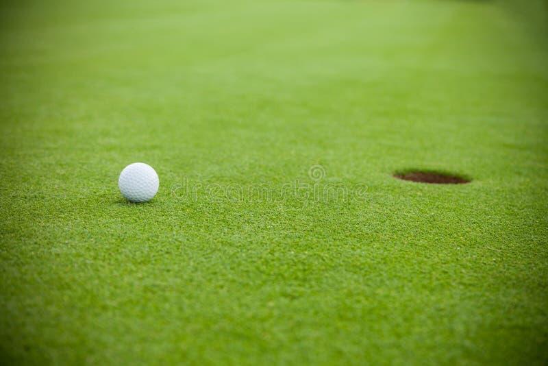 Palla da golf accanto al foro fotografie stock libere da diritti