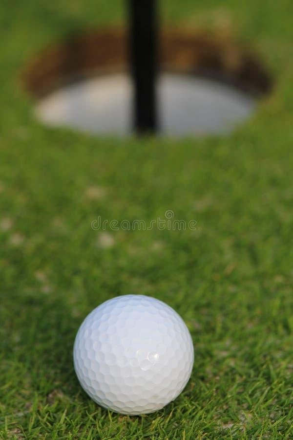 Palla da golf circa da cadere nella tazza, su erba verde immagine stock