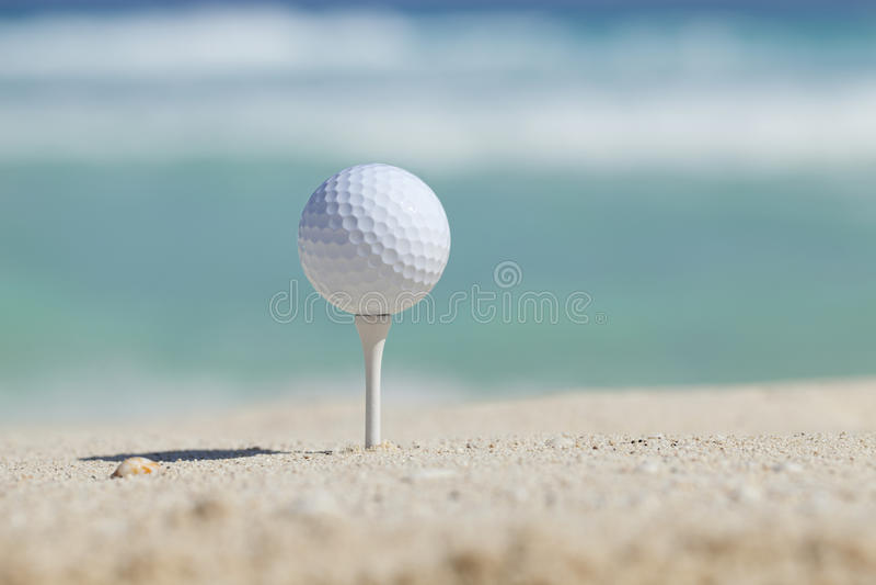 Palla da golf sul T in spiaggia di sabbia con le onde di oceano dietro fotografia stock libera da diritti