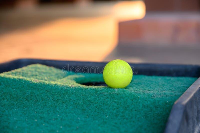Palla da golf verde sulla tazza del foro del bordo sul tiro in buca del prato inglese immagini stock libere da diritti