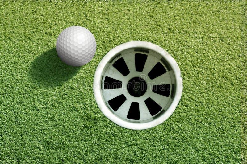 Palla da golf vicino al foro fotografia stock libera da diritti