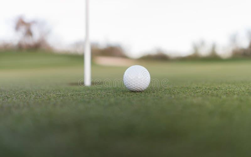 Palla da golf vicino al foro della tazza su verde mettente fotografia stock