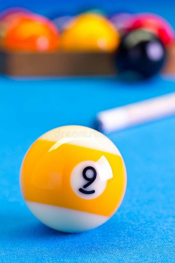 Palla del gioco nove dello stagno del biliardo con la stecca sulla tavola di biliardo fotografia stock libera da diritti