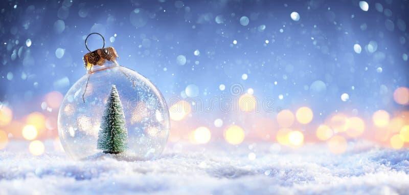 Palla della neve con l'albero di Natale e nelle luci illustrazione vettoriale