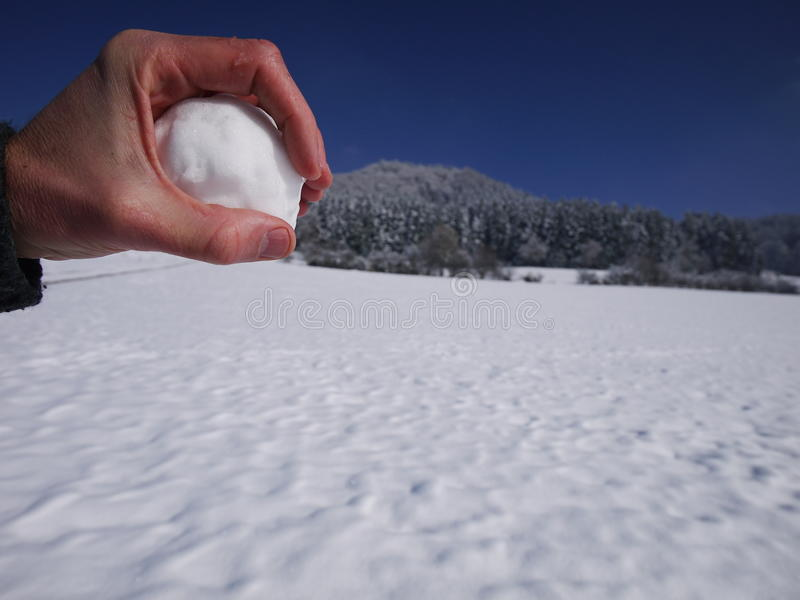 Palla della neve della tenuta della mano immagine stock