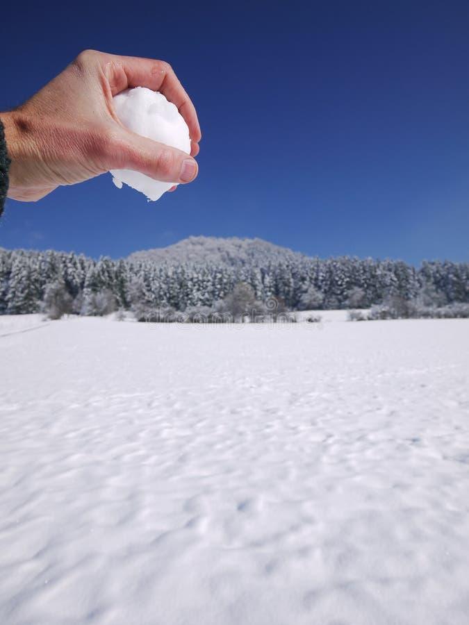Palla della neve della tenuta della mano fotografia stock libera da diritti