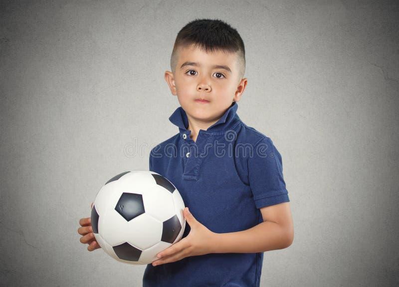 Palla di calcio della tenuta del ragazzo fotografie stock libere da diritti