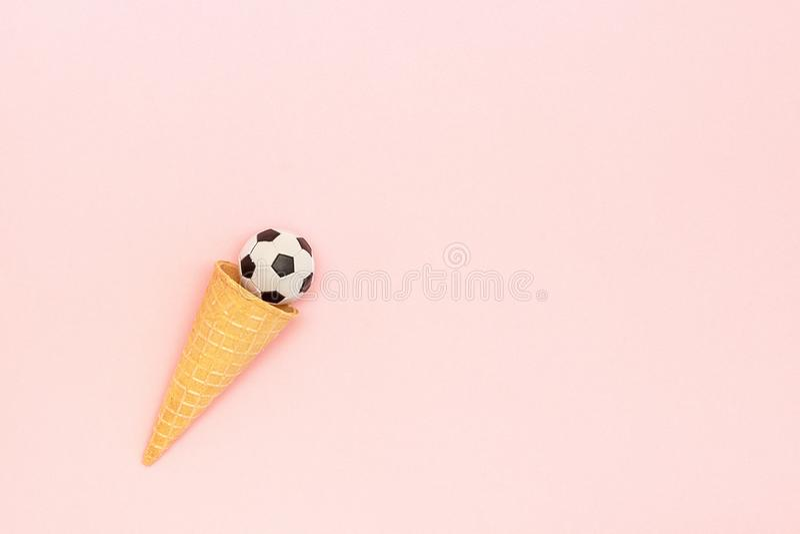 Palla di calcio o di calcio nel cono della cialda del gelato su fondo rosa nello stile minimo Spettacolo di sport di concetto Cop fotografia stock