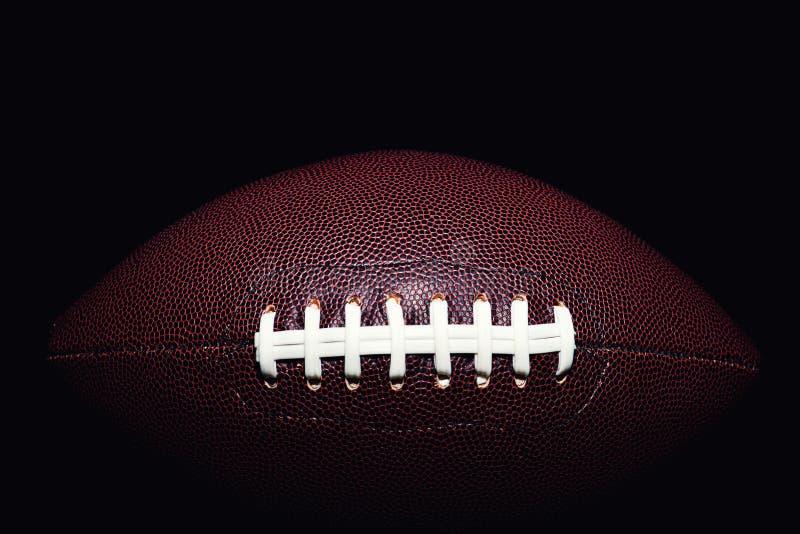 Palla di football americano isolata su fondo nero immagine stock libera da diritti