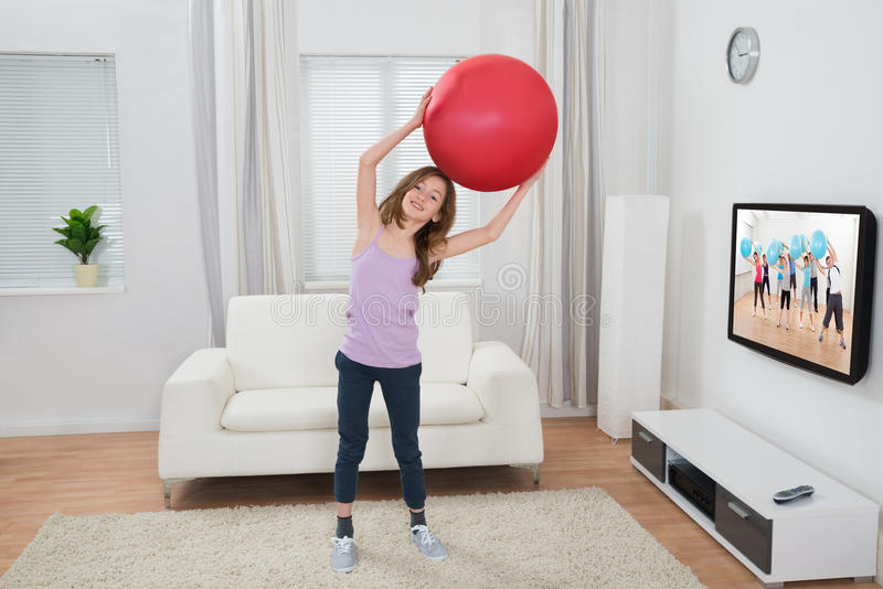 Palla di forma fisica della tenuta della ragazza in Front Of Television immagine stock libera da diritti