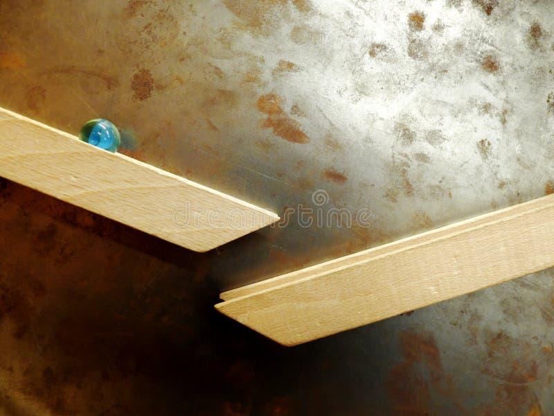 Palla di marmo che rotola giù lungo la ferrovia di legno allegata magneticamente alla parete arrugginita del metallo Il concetto  fotografie stock