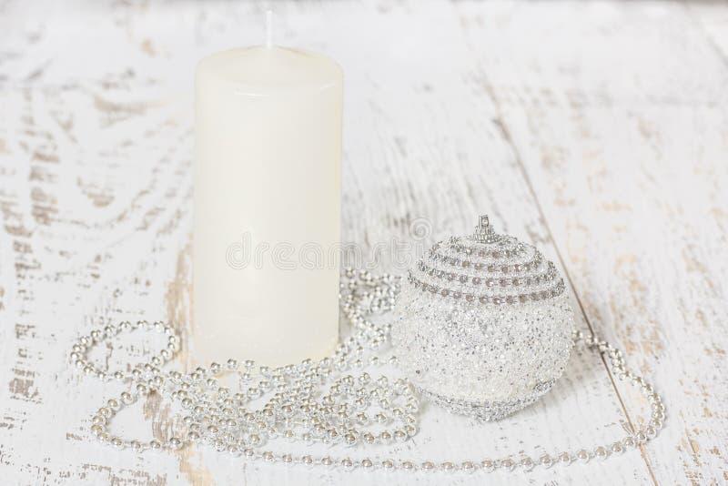 Palla di Natale, candela, perle sui bordi di legno immagine stock