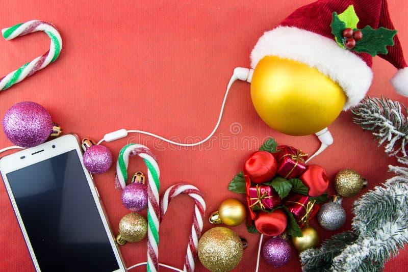 Palla di Natale con il cappello e lo smartphone di Santa con le cuffie, su rosso fotografia stock libera da diritti