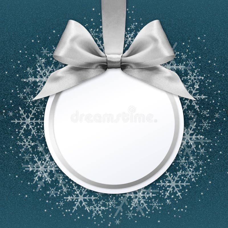 Palla di Natale con l'arco d'argento del nastro del raso sul blu fotografia stock libera da diritti